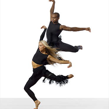 Parsons Dance male and female dancers strike a bird-like pose in front of a white background