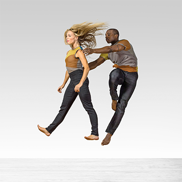 Parsons Dance two dancers in mid-air as if defying gravity looking away from camera in front of white backdrop