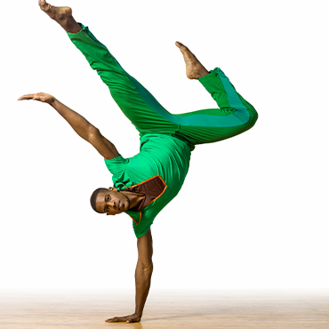 Philadanco! male dancer dressed in green doing a handstand in front of a white wall