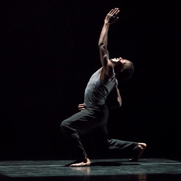 Philadanco! male dance kneeling down on one knee with arms reaching up on stage with black background