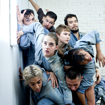Rubberband dancers dressed in blue crawling over each other against a white wall