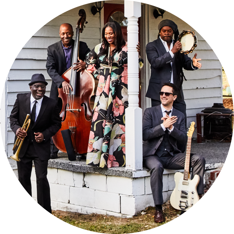 Ranky Tanky dressed formally standing and sitting on a porch with instruments