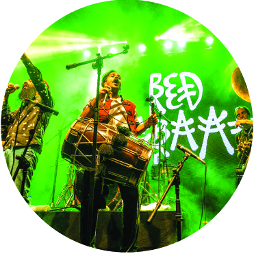 Red Baraat performing with a green backdrop with the Red Baraat logo on the screen behind them
