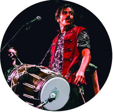 Sunny Jain of Red Baraat performing in a red vest with his dhol drum