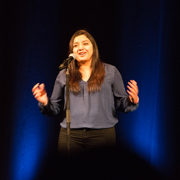 Suitcase Stories female speaker in blue blouse speaking into microphone with arms out in front of black background with blue lighting