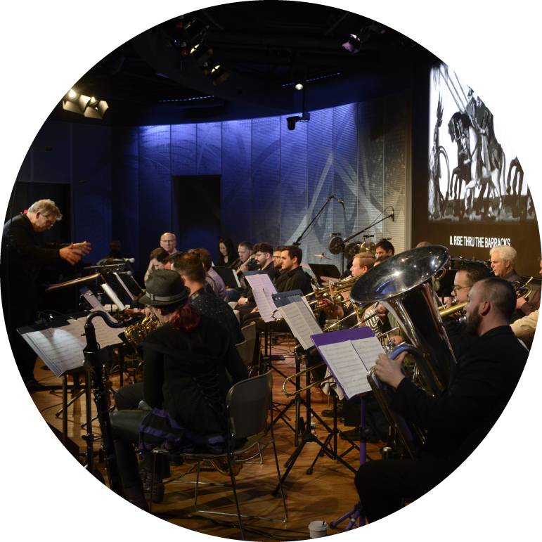 A jazz orchestra of trumpet, tuba, saxophone, and trombone players sit in front of a gray and white projection screen. In front is a light-skinned person in a dark suit conducts them.