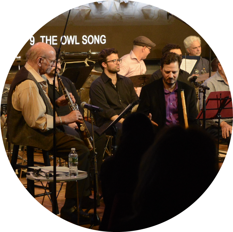 A group of musicians with Mehmet Ali Sanlıkol, a man with with a medium skin tone and short dark hair sitting in front. To his right sits Dave Liebman, a man with light skin and white hair.