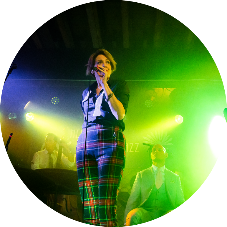 Front woman Elizabeth Bougerol wears a blue top and plaid pants. She sings into a microphone on stage, with green, yellow and blue lights shining behind her.