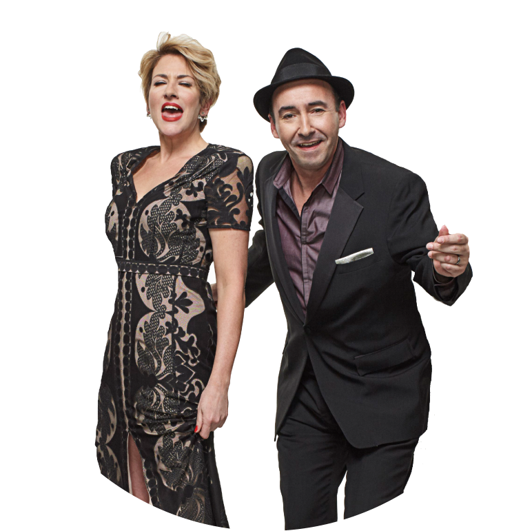Elizabeth Bougerol wears a black and beige lace lace shortsleeve v-neck dress. She sings next to Evan Palazzo who wears a black suit and black hat. They stand against a white background.