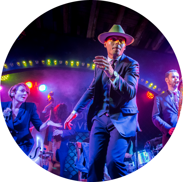 The band performs on stage with purple and blue lights shining on them. One man is towards the front wearing a three piece suit and hat.