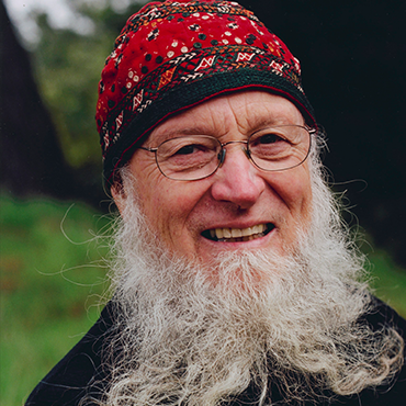 Terry Riley with red beanie smiling at camera in the woods