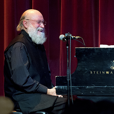 Terry Riley sitting at piano in front of stage curtain while speaking into microphone