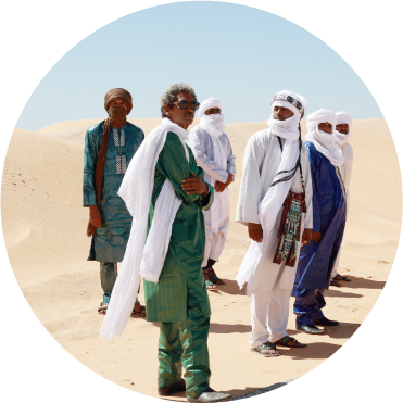 The band stands in tradition Tuareg robes with white scarfs in the desert with a blue sky above them