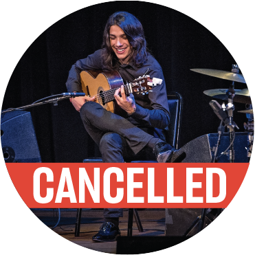 Tomate sitting on stage in all black, playing the guitar, with cancelled banner over the image