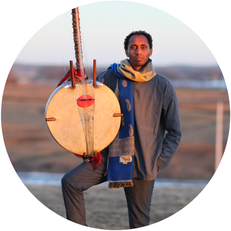 Tunde stands facing the camera with the kora rest on his bent right knee. He wears a blue top, yellow and blue scarf and stands against a landscape backdrop