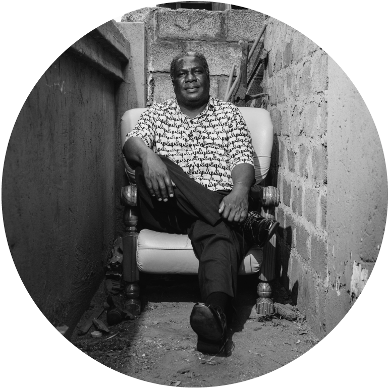 Black and white photograph of Vusi Mahlasela sitting at the end of an alley on a light color chair. His right leg is crossed over the left.