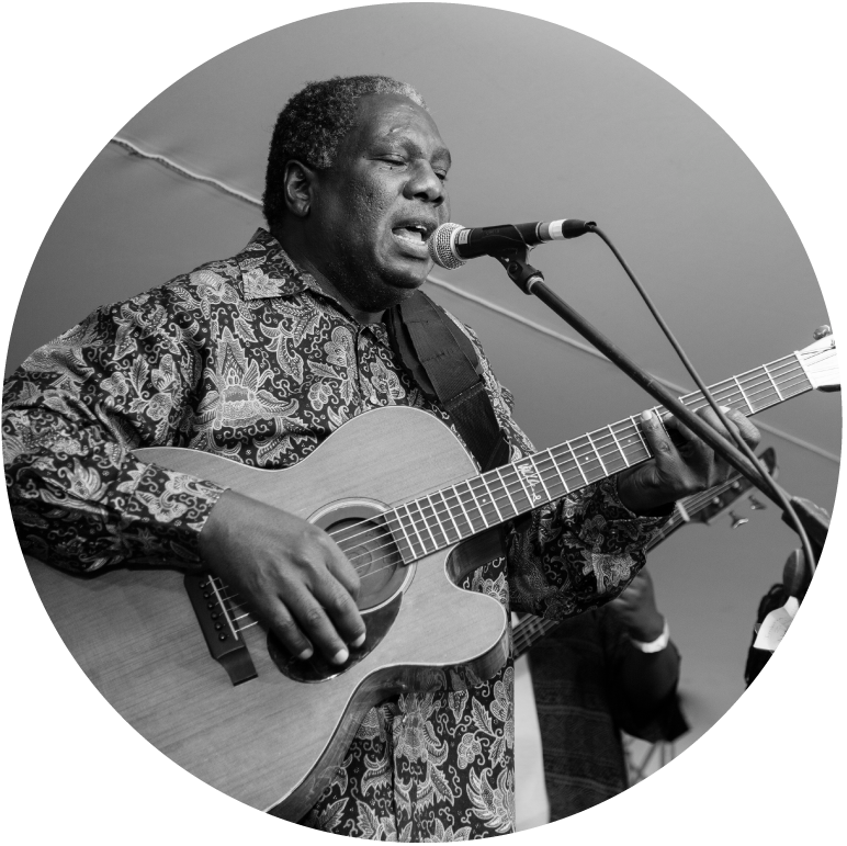 Black and white photo of Vusi playing his acoustic guitar and singing into a microphone