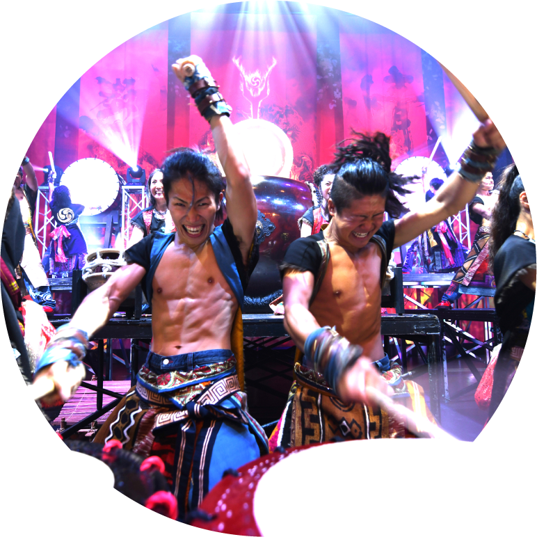 Yamato two drummers with arms raised in air ready to hit taiko