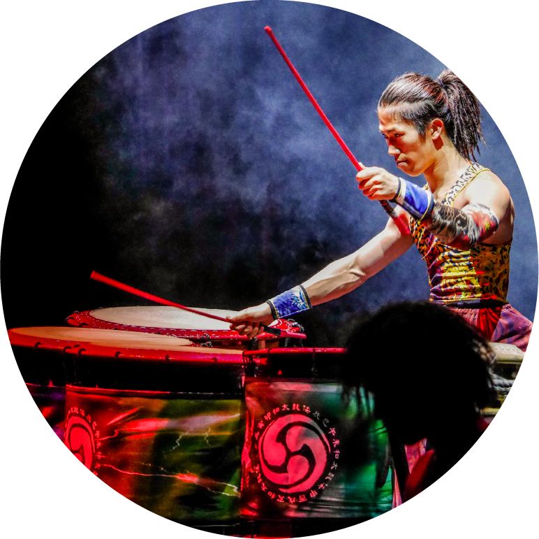 Yamato male drummer holding long stick about to hit taiko lit in red in front of black smoky background