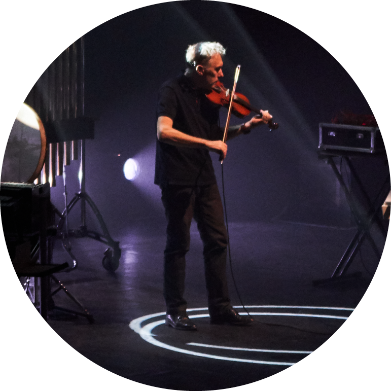 Yann Tiersen stands wearing all black holding a violin. His left arm holds the violin under his chin and his right arm holds the bow. He stands on stage inside a double circle of white light that reflects on the ground.