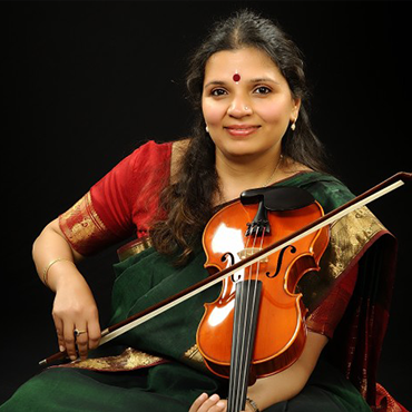 Kala Ramnath wearing traditional Indian attire while holding violin and bow in front of black background