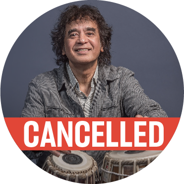 "Zakir Hussain wearing a khaki colored top with his hands hovering over the tabla, with a ""cancelled"" banner over the image"