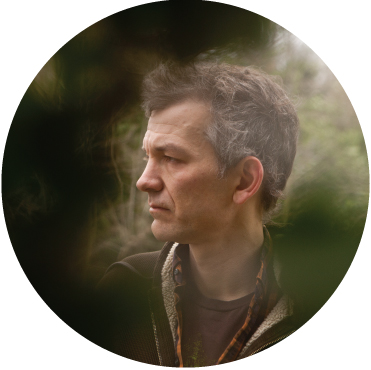 Brad Mehldau captured looking away from the camera thoughtfully through a bush