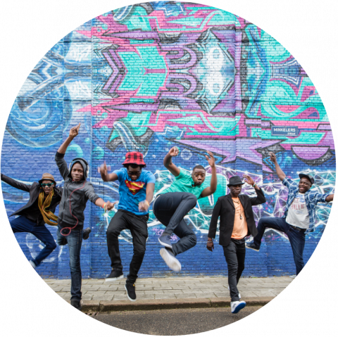 6 members of Mokoomba ecstatically jumping in front of a beautiful pink and blue wall