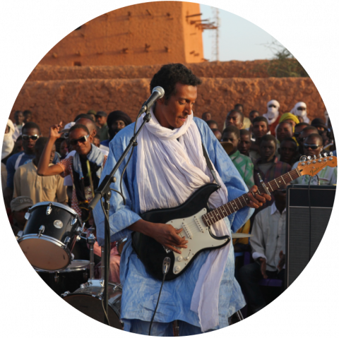 Bombino plays an electric guitar with a microphone on a stand in front of him. He wears a blue and white robe, with many people standing behind him watching.