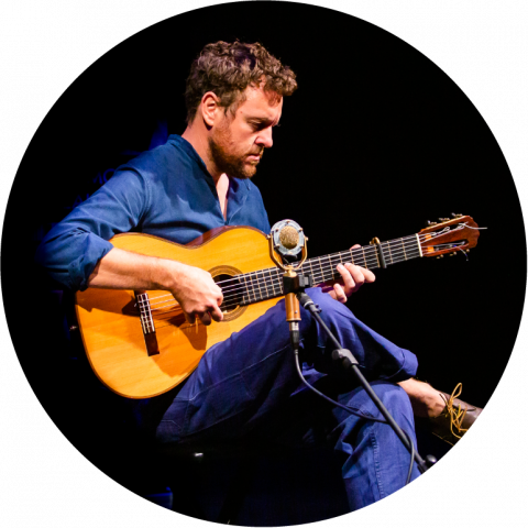 Derek Gripper sits in front of a black background. He is light-skinned with short brown hair and beard. He wears blue shirt and pants and plays an acoustic guitar that is propped up on his leg.