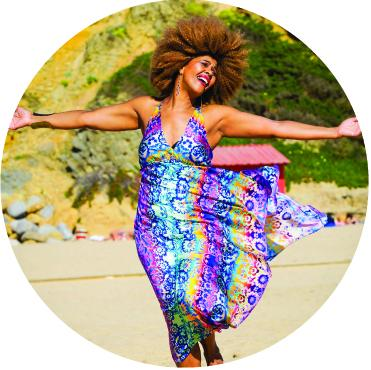 Fantcha standing on the beach with her blue dress blowing in the wind and her arms outstretched at her sides