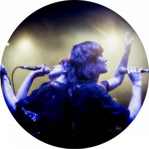 The two singers of Nouvelle Vague stand back to back holding microphones in one hand, with their other hands in the air. Bright white light radiates behind them. They are both dressed in black.