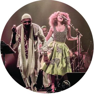Omar Sosa and Yilian Canizares performing live on stage holding hands singing to the audience