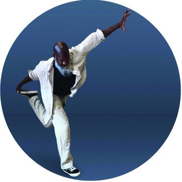 Raphael Xavier wears a white suit with a black undershirt against a blue background. He stands on one foot with his left foot held behind him with his right hand and his left hand extended into the air