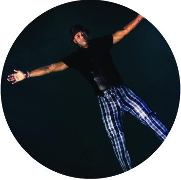 Roberto Fonseca floating in water with arms outspread, wearing plaid pants
