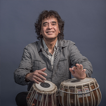 Zakir Hussain wears an olive button up shirt, and is sitting in front of a gray background. Both hands are resting on tablas.