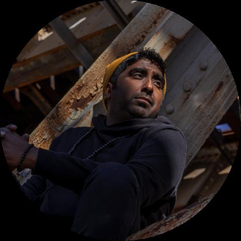 Zeshan B wearing a dark hoodie and sitting under a bridge
