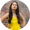 Purnima stands with her arms on her hips with her long brown hair in waves down her yellow tank top that has the words BollyX on it