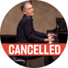 "Brad Mehldau in black attire playing grand piano passionately on stage with a poppy colored ""cancelled"" banner over the photo"