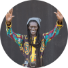 Cheikh Lo in colorful outfit smiling at camera with arms up in the air in front of black wall
