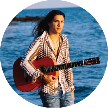 Tomate, standing in front of the backdrop of the ocean, holding his guitar, hair flowing in the wind