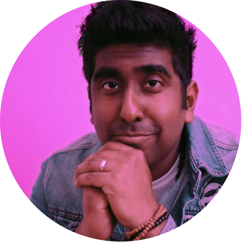 Zeshan B with a pink background looking into the camera with his hands by his face, clasped